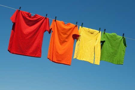 ropa colgada: Alegre ropa de verano. Camisetas de colores en una l�nea de ropa y el cielo azul.