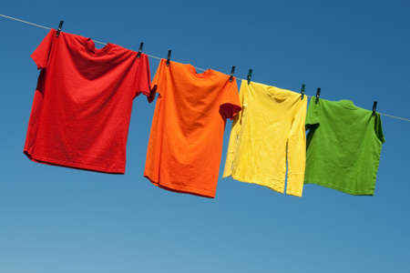 clean clothes: Joyful summer laundry. Colorful t-shirts on a laundry line and blue sky.
