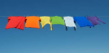 laundry: Rainbow laundry. Bright shirts on a clothesline on a blue sky background. Stock Photo