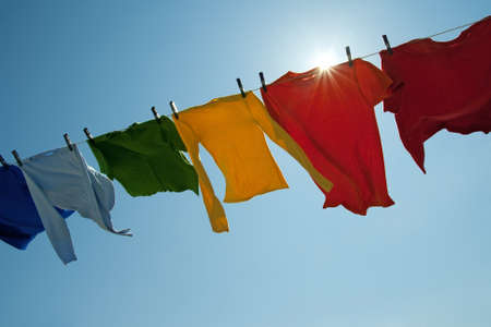 Sun shining over a laundry line with bright clothes on a windy day. photo