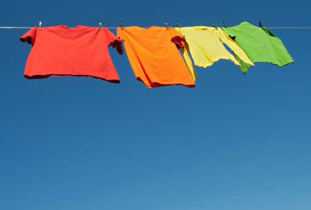 Bright clothes on a laundry line and blue sky with copy space. photo