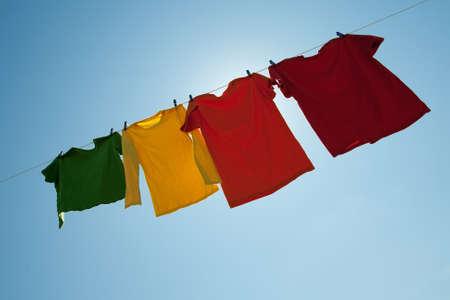 照らす: カラフルな服に青い空を背景に、ランドリー ラインの背後にある太陽の光。