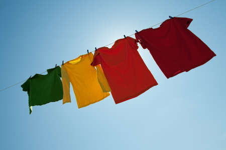 drying: Sunshine behind colorful clothes on a laundry line, on blue sky background.