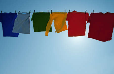Sun shining through colorful clothes drying in the wind in the blue sky. Standard-Bild