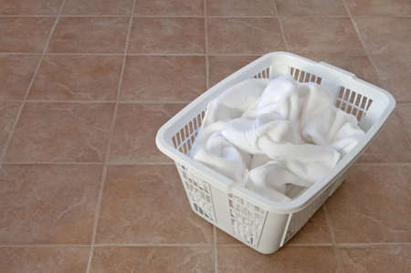 room for text: White towels in a laundry basket on ceramic floor, in a laundry room or bathroom.