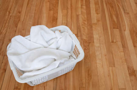 indoors: Clean white towels in a laundry basket, on a wooden floor indoors. Stock Photo