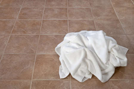 messy: Creased white towels on ceramic floor in a laundry room or bathroom. Stock Photo