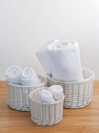 terry: Clean towels in white wicker baskets, on a wooden surface.