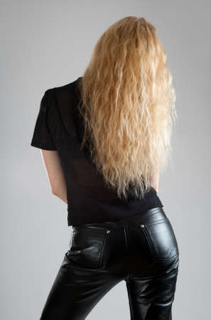 Girl in black leather pants, with beautiful long hair.