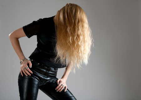 Girl in black leather pants, showing up her beautiful long hair.