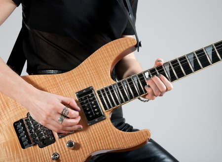 Female guitarist playing hard rock style electric guitar. photo