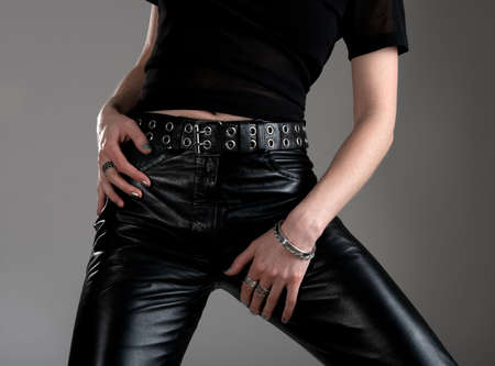 Young woman in black leather pants, wearing metal jewellery.