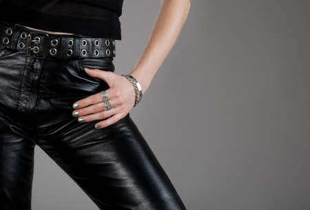 Close-up of black leather pants and hand with silver jewellery.