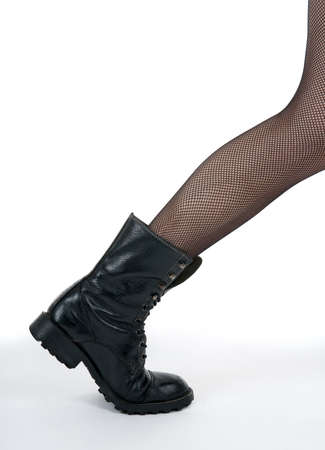 Female leg in black army boot stepping out of the picture. photo