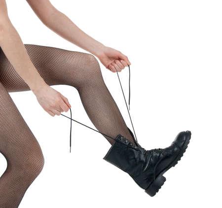feministische: Meisje in sexy panty vetersluiting haar leger-stijl zwarte laarzen. Stockfoto