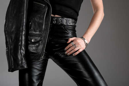 Person wearing black leather pants and jacket with zippers. Stock Photo