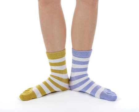 odd: Funny legs in socks of different colors on white background.