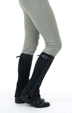 Woman wearing horse riding boots and breeches, on white background.