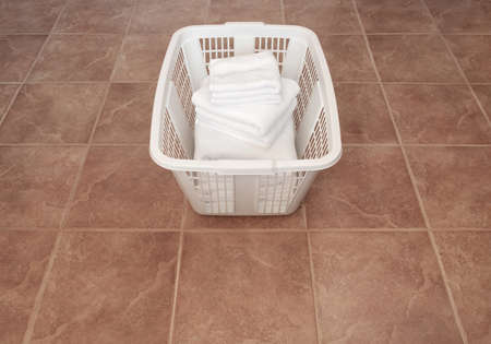 Laundry  Clean white towels in a laundry basket on ceramic floor