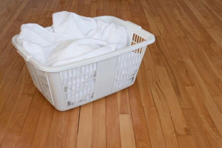 indoors: Laundry basket with clean white towels, on a wooden floor indoors