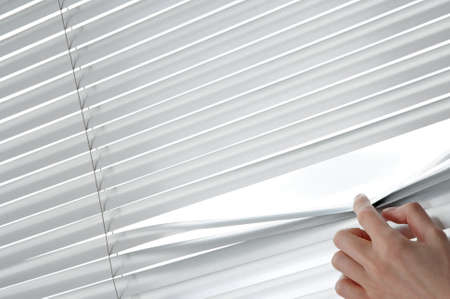 Female hand separating slats of venetian blinds with a finger to see through  photo