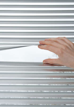 Female hand opening metallic venetian blinds for peeking