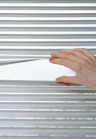 view through: Female hand opening metallic venetian blinds for peeking