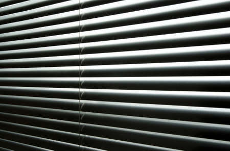 jalousie: Daylight coming through closed metallic blinds, high-contrast abstract pattern