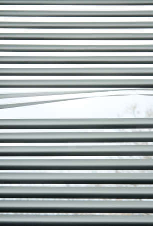 see through: Peeking through the slats of venetian blinds  Stock Photo