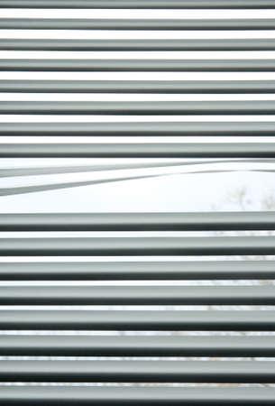 Peeking through the slats of venetian blinds  Standard-Bild