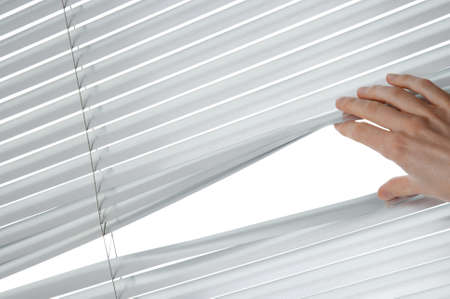 a blind: Female hand separating slats of venetian blinds to see through