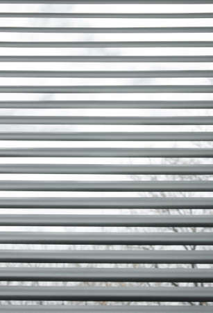 venetian blind: Trees seen through semi-closed metallic blinds on a window