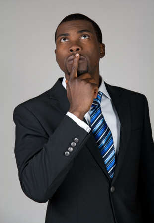 African American businessman looking up and thinking, holding a finger on his lips  Standard-Bild