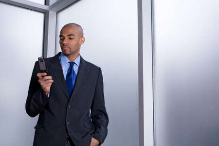 Businessman beside an office window, dialing a number on his cell phone Stock Photo - 12972851