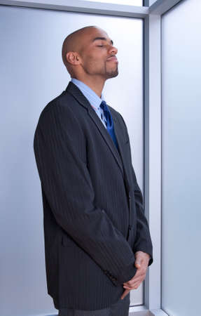 eye's closed: Businessman looking zen, standing with his eyes closed near a window