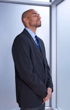 ojos cerrados: Empresario busca zen, de pie con los ojos cerrados cerca de una ventana