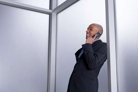 Businessman talking on his cell phone and smiling, beside an office window  photo