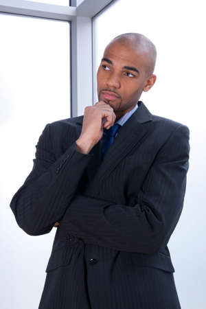 mulatto: Portrait of a thoughtful young businessman beside a window