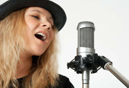 Young woman in black hat singing with studio microphone  Isolated on white background  photo