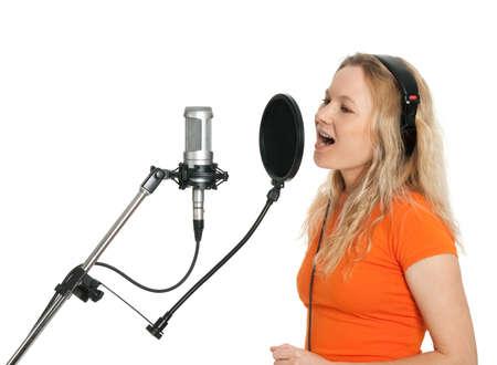 gente cantando: Cantante femenina en la camiseta naranja cantando con micr�fono de estudio aislado sobre fondo blanco Foto de archivo