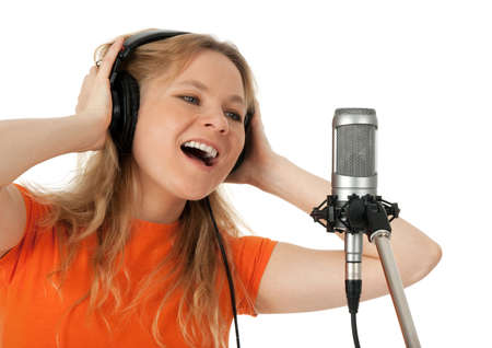 singing girl: Young woman in orange t-shirt singing with studio microphone  Isolated on white background  Stock Photo