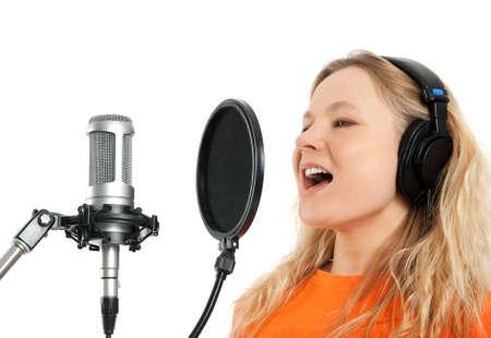 estudio de grabacion: Cantante femenina en los auriculares cantando con micr�fono de estudio aislado sobre fondo blanco Foto de archivo