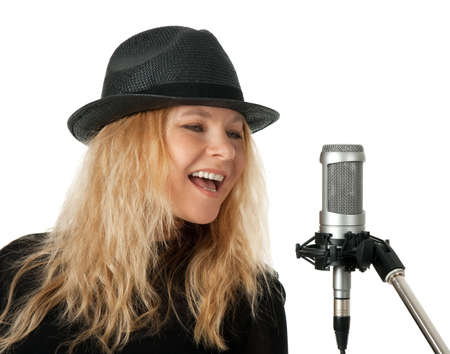 Female singer in black hat singing with studio microphone  Isolated on white background  photo