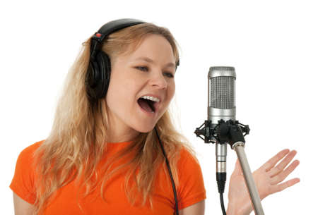 Female singer in headphones singing with the microphone  Isolated on white background  photo