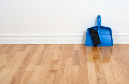 Blue dustpan and brush near the white wall on a wooden floor, with copy space  Stock Photo