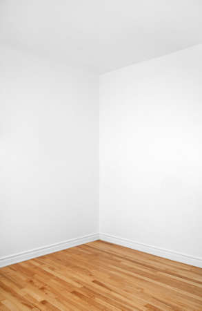 Empty corner of a renovated room with white walls and wooden floor