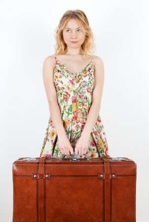 Girl wearing summer dress holds a vintage suitcase, anticipating travel  photo