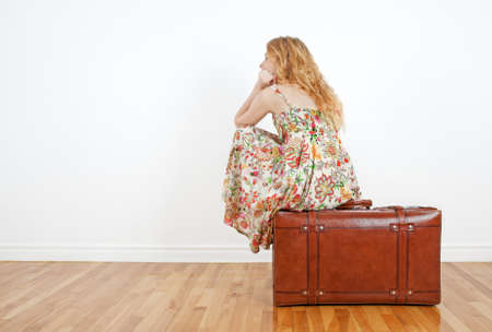 Girl wearing summer dress sits on a vintage suitcase, anticipating travel and waiting  photo