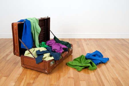 messy room: Leather suitcase on a wooden floor in an empty room, full of colorful clothing