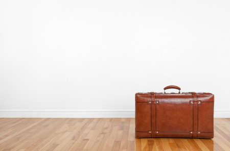 valise voyage: Valise en cuir vintage sur un plancher en bois dans une pièce vide Banque d'images